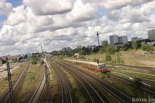 An S-bahn train shoots pass east Berlin under a blanket of clouds. .