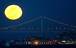 San Francisco Fisherman's Wharf and the Oakland Bay Bridge had a  full moon as a backdrop.