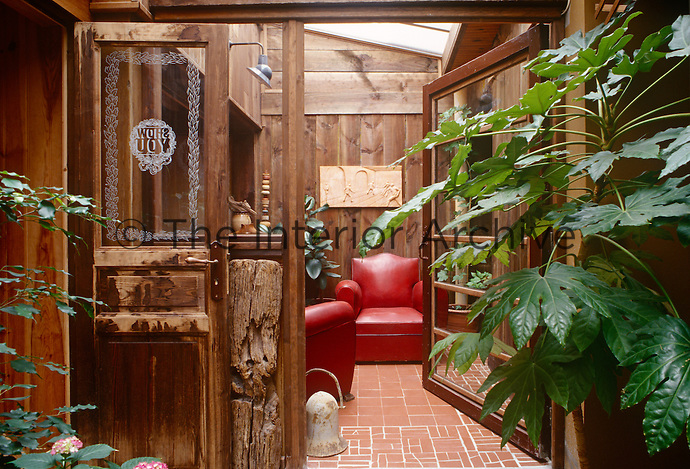 A cosy sitting area is glimpsed through antique glass doors opening from the entrance hall