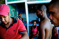 Fish salesmen play dominoes for money and beers after work on the Stabroek Market docks in Georgetown, Guyana. A lack of infrastructure connecting Guyana to continental South America has isolated the country, one of the poorest in the western hemisphere, from potential trade opportunities. Government plans to pave the 350 mile road from Georgetown, its coastal capital, to its southern border are expected to open Guyana to booming trade with neighboring Brazil, a buying super power in South America with 200 times the population of Guyana.