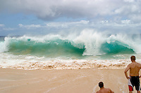 Men watch a wave breaking at Sandy Beach on the South shore of Oahu