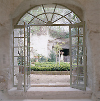 View through the double French windows of the barn into the gravelled courtyard garden