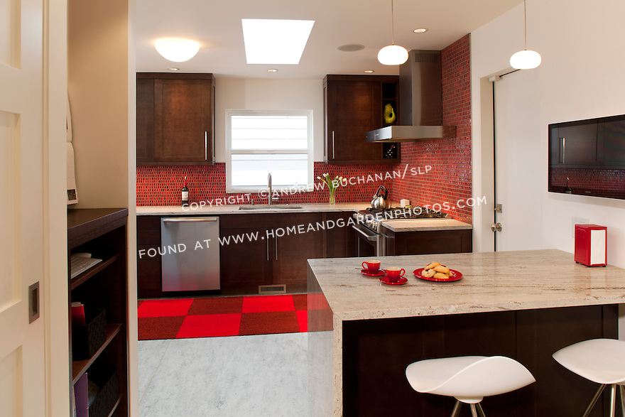 Red tiles provide a burst of color in this bold, contemporary kitchen remodel. This image is available through an alternate architectural stock image agency, Collinstock located here: http://www.collinstock.com