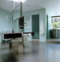 Milk-glass tiles and cherry wood counters are used in this minimal industrial-style master bathroom