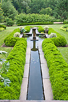 Water garden feature with boxwood Buxus, fountain, lawn grass, evergreen trees and shrubs, cement urn planters containers, hedging