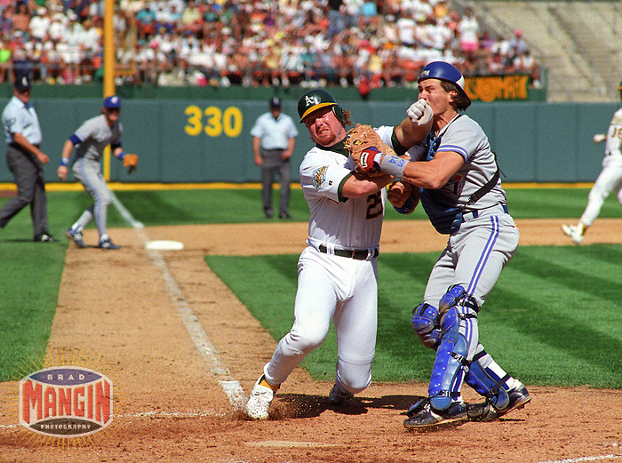 Baseball: Oakland Athletics Mark McGwire and Toronto Blue Jays Pat Borders in action during the ALCS. Oakland, CA 10/8/1992 MANDATORY CREDIT: Brad Mangin/Sports Illustrated