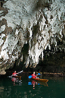 Raja Ampat Archipelago, West Papua, Indonesia, December 2010. A giant bat cave with stalactites leaking out of the Carstic limestone rock is our shelter during a heavy thunderstorm. Thousands of small islands fringed by coral reefs and blue water mangroves litter the Raja Ampat archipelago. The turquoise and blue waters are teeming with marine life that forms the livelihood for the local Papuan population. The Raja Ampat Research & Conservation Centre (RARCC) supports the locals to develop a community based, sustainable tourism project, inviting visitors to explore their islands by sea kayak and experience the culture by staying amongst the local people in traditional style homestays. Photo by Frits Meyst/Adventure4ever.com