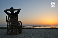 Man on chair watching sunrise  over sea, Red Sea, Egypt (Licence this image exclusively with Getty: http://www.gettyimages.com/detail/81865728 )