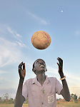 A boy bounces a soccer ball on his head in the Southern Sudan town of Yei.