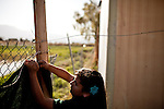 Eleven-year-old Melanie Salgado fixes fencing in the Rancho Garcia trailer park in Thermal, Calif., March 9, 2012.