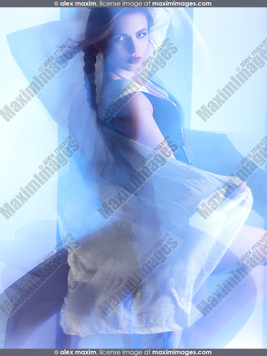 Futuristic dynamic high fashion photo of a young woman in trendy clothes posing in shiny neon light settings. The photo was not digitally manipulated.