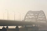 Foto: VidiPhoto<br /> <br /> HEDEL - De Hedelse brug over de Maas in de mist maandag. De dichte tot zeer dichte mist in het hele land zorgde maandag voor enorme verkeersoverlast. Het verkeer stond rond 8.00 uur over ruim 300 kilometer vast. Dat is twee keer zo druk als op een normale maandagochtend. Op diverse snelwegen bleven de spitsstroken maandagochtend dicht. Het KNMI gaf zondagavond al code geel af voor het hele land. Het zicht was soms minder dan 100 meter. Maandagavond breiden de mistbanken volgens Weeronline weer uit en daalt het zicht flink. Dinsdagochtend kan het wegverkeer opnieuw last hebben van slechte zichtwaarden. Door de mist werden ook verschillende vluchten van en naar Schiphol geannuleerd.
