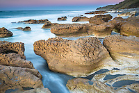 Pastel colours of dusk on beautiful rocky beach with limestone formations at Paturau on west coast of South Island, Nelson Region, New Zealand, NZ