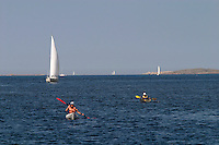 People in kayaks and sailboats on the water.