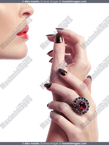 closeup of woman hands with fancy nail polish and a red stone ring