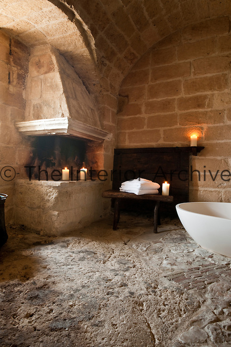 A fireplace in the corner of this bathroom at the unique Albergo Diffuso Le Grotte della Civita in Southern Italy, housed in  restored caves