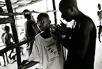 A former combatant threatens a young boy with a toy gun..Monrovia, Liberia, January 1998