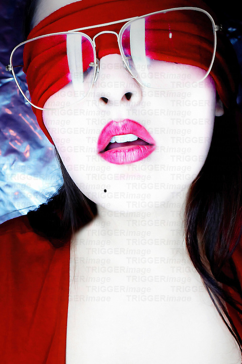 The face of a young woman with pink lipstick her eyes covered with a red blindfold wearing large glasses