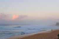 Man walks along beach with surfboard as sun sets. Clouds turn pink as the sun sets.