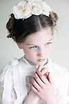 Headshot of young girl with  clear blue eyes and blonde hair wearing white lace looking pensive