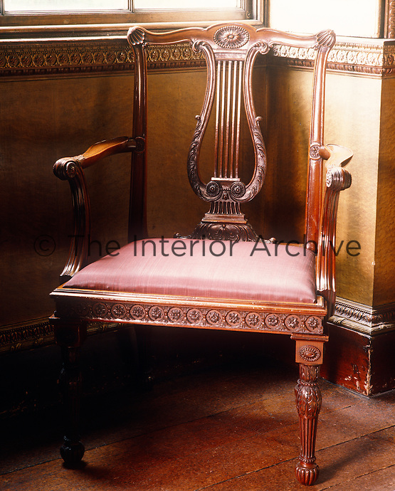 A late 18th century wooden chair is carved with a lyre decoration