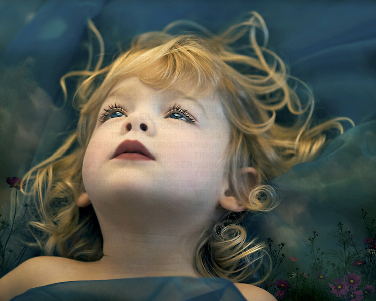A young girl with long blonde wavy hair staring into the blue