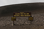 Mauna Kea, Big Island of Hawaii, Hawaii; a wooden sign designating the boundary for the Mauna Kea Icea Age Natural Area Reserve sits alongside the road leading to the summit of the Mauna Kea Observatories (MKO), currently there are 13 independent multi-national astronomical research facilities located on the summit. Mauna Kea's altitude and isolation in the middle of the Pacific ocean make it an ideal location for astronomical observation.