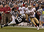 Oakland Raiders linebacker Eric Barton (50) dives in an attempt to stop San Francisco 49ers wide receiver Terrell Owens (81) on Sunday, November 3, 2002, in Oakland, California. The 49ers defeated the Raiders 23-20 in an overtime game.