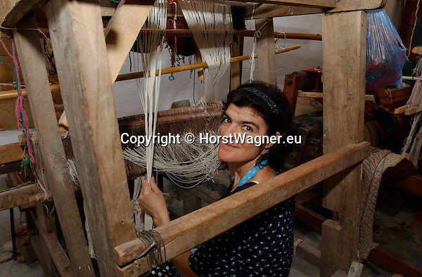 Zogaj-Shkodra/Shkoder-Albania - August 06, 2004---Female weaver working on a carpet at a loom in a private weaving mill;  project area of GTZ-Wiram-Albania (German Technical Cooperation, Deutsche Gesellschaft fuer Technische Zusammenarbeit (GTZ) GmbH); economy-industry-enterprise-labour-people---Photo: © HorstWagner.eu