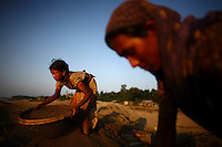 Women and children work sifting sand at Bhollar Ghat. At least 10,000 people, including 2,500 women and over 1,000 children, are engaged in stone and sand collection from the Bhollar Ghat on the banks of the Piyain river. Building materials such as stone and sand, and the cement which is made from it, are in short supply in Bangladesh, and commands a high price from building contractors. The average income is around 150 taka (less than 2 USD) a day.