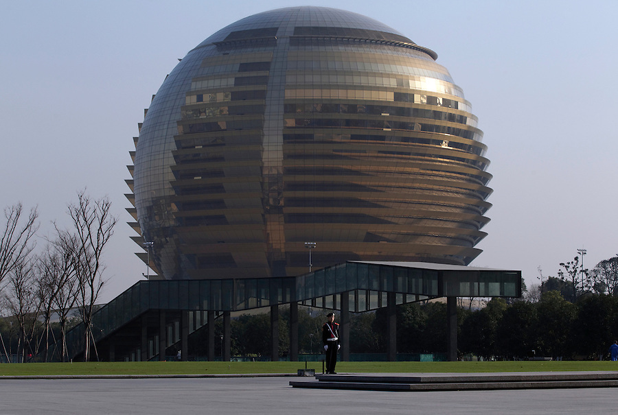 A security guard keeps watch in front of the Intercontinental Hotel, which has been built in the shape of a golden ball in Hangzhou.