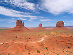 Mittens in Monument Valley, Navajo Tribal Park, Arizona, USA. Winding unpaved road and red sandstones outcrops.