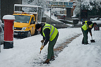 Council workers clear the pavement outside local shops.