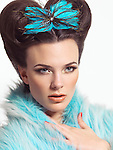 Beautiful young woman with gorgeous hairstyle wearing a blue fur coat