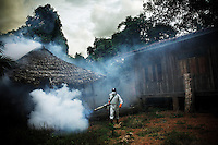 A man is fogging a Karen village against mosquitoes in Northern Thailand. The technique of fogging, or area spraying, which aims at killing mosquitoes by contact with the insecticide in the air, has had very limited success in malaria control.