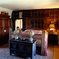This bedroom is decorated with tartan blankets giving it a distinctly Scottish emphasis