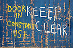 "The words ""keeep (mis-spelled) clear .. door in constant use"" has been painted by hand on an entrance to a now derelict building that is soon to be developed into new apartments. Peeled blue gates has been rubbed away to reveal the old wood in the once-industrial Tetley Street near Bradford city centre, Yorkshire."