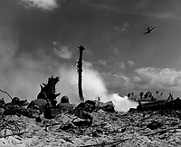 An American plane sweeps overhead to strafe the enemy hidden in their coral trenches, while a group of Marines lie prone in the sand peppering the Japs across smoking NoMan's Land with rifle fire.  Eniwetok Atoll, Marshall Islands, February 1944.  (Coast Guard)<br /> Exact Date Shot Unknown<br /> NARA FILE #:  026-G-3364<br /> WAR &amp; CONFLICT BOOK #:  1184