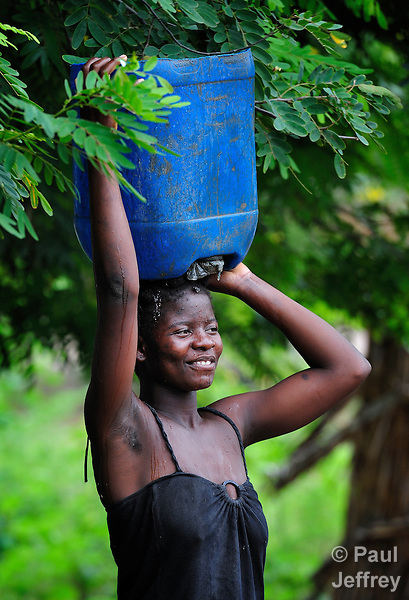 """A young woman carries water in Chidyamanga, a village in southern Malawi that has been hard hit by drought in recent years, leading to chronic food insecurity, especially during the """"hunger season,"""" when farmers are waiting for the harvest."""