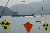 SURROUNDED BY JAPANESE POLICE AND COAST GUARD GREENPEACE INFLATABLES &quot;PROTEST&quot; ( bear witness...) , BENEATH KITES FROM THE ARCTIC SUNRISE, IN UCHIURA BAY, BESIDE THE TAKAHAMA NUCEAR PLANT, AS BNFL SHIP 'PACIFIC PINTAIL' DEPARTS LATE AFTERNOON AFTER COLLECTING REJECTED PLUTONIUM MOX FUEL, FOR SHIPMENT BACK TO THE UNITED KINGDOM. TAKAHAMA, JAPAN. 04/07/02. .PIC &copy; JEREMY SUTTON-HIBBERT/GREENPEACE 2002..*****ALL RIGHTS RESERVED. RIGHTS FOR ONWARD TRANSMISSION OF ANY IMAGE OR FILE IS NOT GRANTED OR IMPLIED. CHANGING COPYRIGHT INFORMATION IS ILLEGAL AS SPECIFIED IN THE COPYRIGHT, DESIGN AND PATENTS ACT 1988. THE ARTIST HAS ASSERTED HIS MORAL RIGHTS. *******
