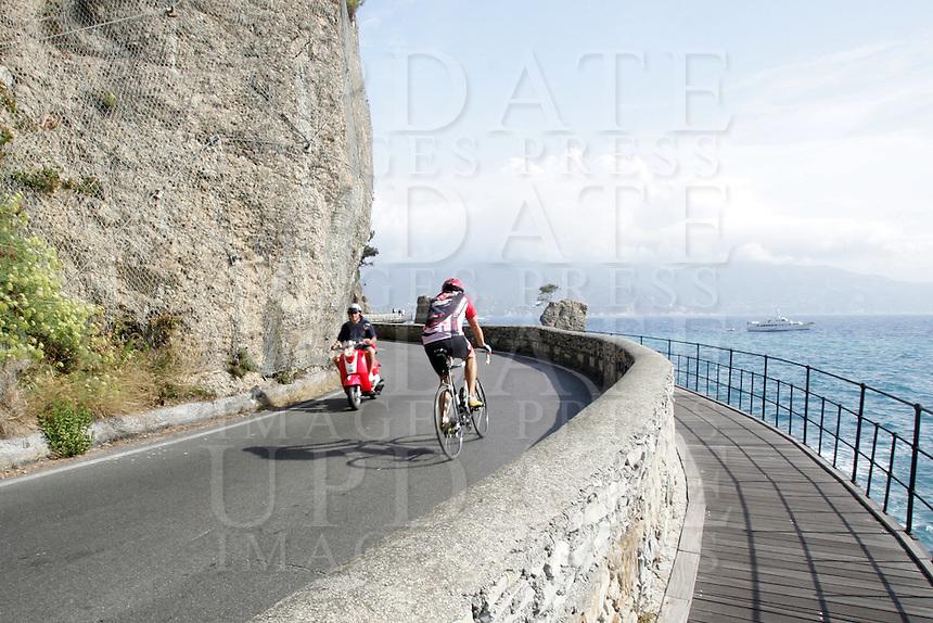 Uno scorcio della strada panoramica tra Portofino e Santa Margherita Ligure.<br /> A cyclist and a biker make their way along the corniche road from Portofino to Santa Margherita Ligure, Liguria, Northern Italy.<br /> UPDATE IMAGES PRESS/Riccardo De Luca