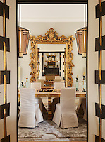 An 18th-century Italian gilt mirror takes centre stage in a luxurious dining room; the table is made of oak and bronze, and the chairs are slip- covered in Egyptian linen. The open doors are black-stained oak covered in Fortuny silk and adorned with bronze belts.