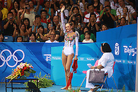 August 23, 2008; Beijing, China; Rhythmic gymnast Anna Bessonova of Ukraine waves to fans after receiving ribbon score with coach Albina Deriugina on way to winning bronze in the All-Around final at 2008 Beijing Olympics..