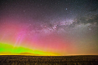 A weak display of Northern Lights with red-pink upper curtains, in the northeast with the summer Milky Way rising in the east, taken from home overlooking a springtime field. Taken with the Canon 5D MkII and 14mm Samyang lens in a single exposure at f/2.8 and ISO 1600, tracked on the iOptron SkyTracker. Taken in the early morning hours of May 6, 2013.