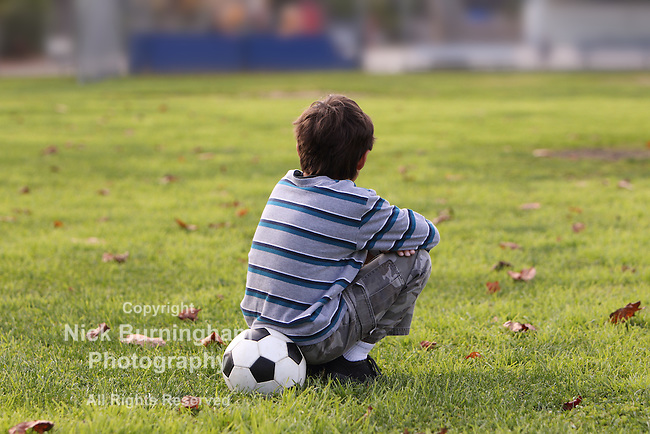 Young boy sits on a soccer ball in a field