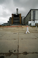 Chernobyl plant worker Sergei Koshelev crosses the high-radiation zone beside Chernobyl's ground zero. The concrete and lead Sarcophagus encloses the ruins of the reactor hall where the meltdown occurred. The Sarcophagus leaks and is structurally unstable. Construction workers preparing foundations for a replacement &quot;New Safe Confinement&quot; can hit their maximum daily dose in two to three hours.  <br /> ------------------- <br /> This photograph is part of Michael Forster Rothbart's After Chernobyl documentary photography project.<br /> &copy; Michael Forster Rothbart 2007-2010.<br /> www.afterchernobyl.com<br /> www.mfrphoto.com <br /> 607-267-4893 o 607-432-5984<br /> 5 Draper St, Oneonta, NY 13820<br /> 86 Three Mile Pond Rd, Vassalboro, ME 04989<br /> info@mfrphoto.com<br /> Photo by: Michael Forster Rothbart<br /> Date: 7/2009    File#:  Canon 5D digital camera frame 72232<br /> ------------------- <br /> Original caption: .Sergei Koshelev, videographer for the Chernobyl SIP PMU (Shelter Implementation Plan Project Management Unit) visits the high-radiation zone just west of the Chernobyl Nuclear Power Plant's 4th Block Shelter (also called the Sarcophagus). Workers refer to the area inside the final high-security perimeter as the &quot;local zone,&quot; where they are doing groundwork for construction of the New Safe Confinement super-structure that will replace the Sarcophagus..