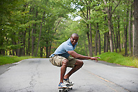 Young man skateboarding down a tree lined street