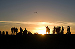 People watching the sunset at Venice Beach as coast guard helicopter flies past.