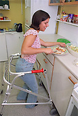 Teenage girl with physical disability preparing sandwich in kitchen of residential respite care home.  MR