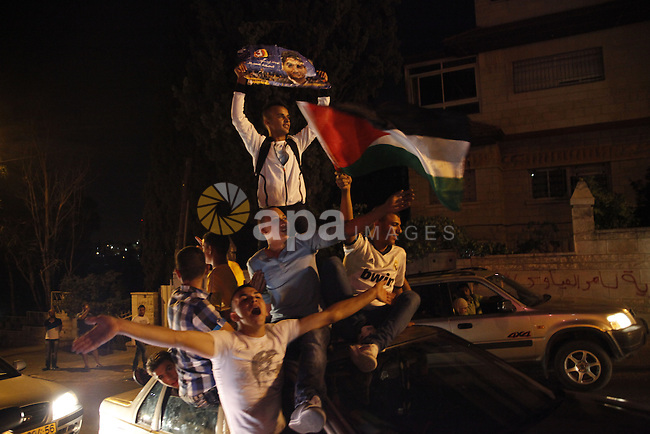 Palestinians celebrate after Palestinian singer Mohammed Assaf won a regional TV singing contest, in Jerusalem, June 22, 2013. Palestinians relished a rare moment of pride and national unity Saturday after the 23-year-old wedding singer from a refugee camp in the Gaza Strip won Arab Idol, a regional TV singing contest watched by millions of people. Photo by Saeed Qaq